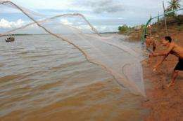 A Cambodian man throws his net into the Mekong river on the outskirts of Phnom Penh in 2011
