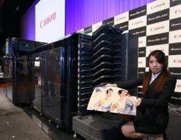 A Canon representative displays a high-speed inkjet printer at the company's Tokyo HQ in February 2011