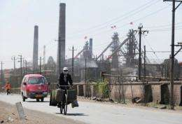 A cyclist wears a protective face mask while passing dozens of factories processing rare earths, iron and coal