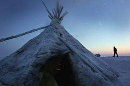 A local Nenets reindeer herder passes by his tent at a camp in Tundra, Russia in 2008