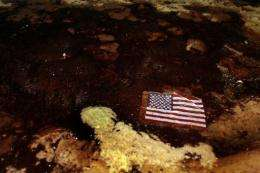 An American flag lays in a slick of oil that washed ashore from the Deepwater Horizon spill in 2010