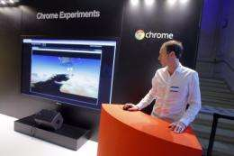 """An employee stands next to a giant screen for """"Chrome Experiments"""""""