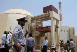 An Iranian security man stands next to journalists outside the reactor building