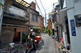 A postman drives a motorcycle through a narrow alley to deliver mail in Tokyo's Sumida district