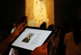 A woman uses an iPad with information on Austrian artist Gustav Klimt