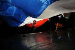 Children play under a giant French flag during a campaign meeting in Paris