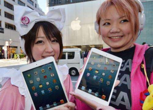 "Customers show their newly purchased ""iPad mini"" tablets from an Apple store"