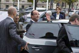 French President Francois Hollande waves as he leaves an environmental conference in Paris