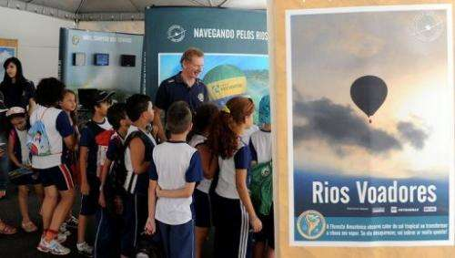 """Gerard Moss (C) talks to children during an exhibition of his """"Rios Voadores"""" (Flying Rivers) project"""
