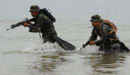 Members of Philippine marines reconaissance team run from the sea during a military exercise