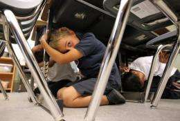 Third grade students take cover under desks as they participate in an earthquake drill in 2011