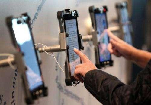 Visitors scroll through e-books for children at the 64th Frankfurt Book Fair in Frankfurt, Germany