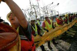 Workers unload oil boom lines to be laid by local fishermen in May 2010 in Hopedale, Louisiana