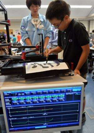 """A boy writes a Chinese letter for """"study"""" with a calligraphy robot at Keio University in Yokohama on July 30, 2013"""
