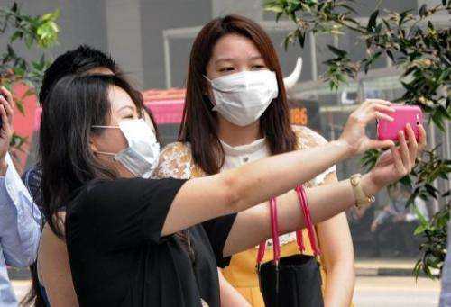 A group of office workers wearing face masks take a picture in Singapore on June 20, 2013