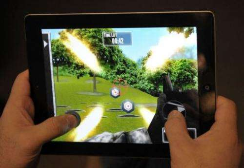 """A man plays the newly released National Rifle Association (NRA) iPhone/iPad app, """"NRA: Practice Range"""""""