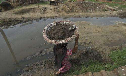An Indian woman carries a basket of human excrement after cleaning toilets in Nekpur, Uttar Pradesh, on August 10, 2012