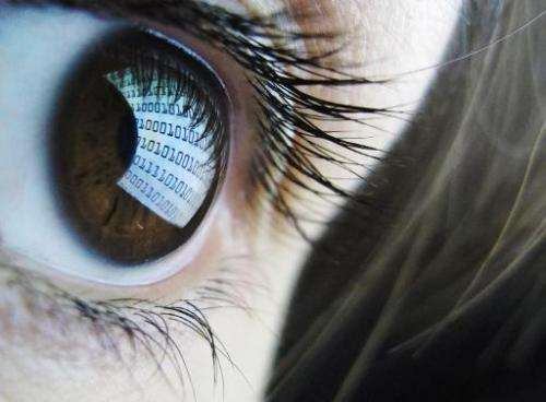 Binary code reflected from a computer screen in a woman's eye on October 22, 2012