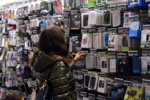 Customers look at mobile phone accessories at a shop on November 27, 2012 in Paris