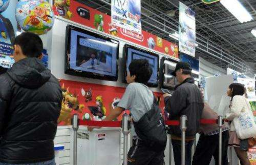 Customers play Nintendo's portable videogame console at a Tokyo electronics shop on October 30, 2013