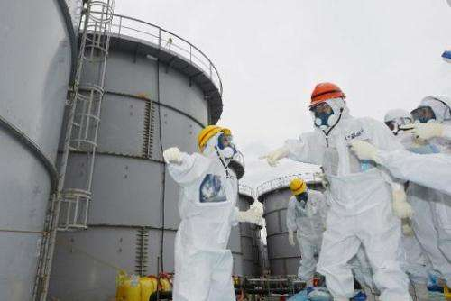 Fukushima Governor Yuhei sato (3rd R) inspects contaminated water tanks at the Fukushima nuclear power plant on October 15, 2013
