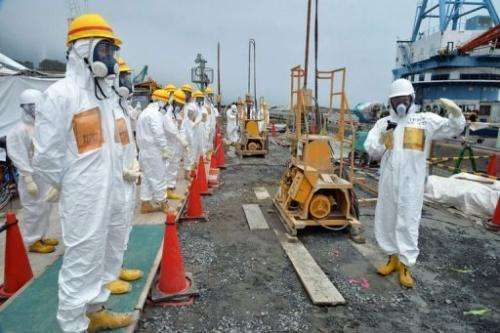 Officials inspect a construction site set up to prevent the seepage of contaminated water into the sea at Fukushima