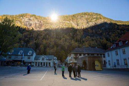 People gather on a spot in front of the town hall of Rjukan, Norway, on October 18, 2013