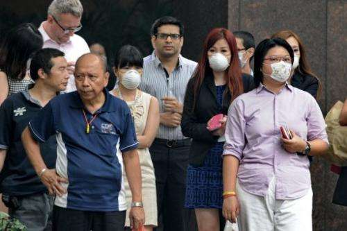 People wear face masks in Singapore on June 20, 2013