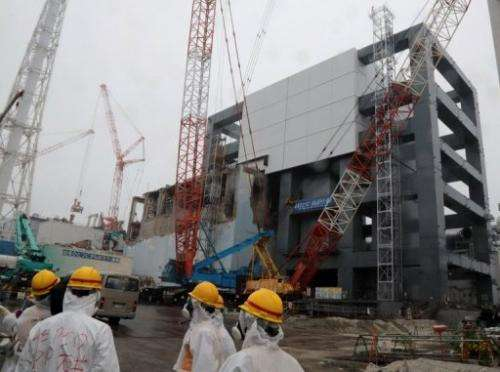 Reporters and Tokyo Electric Power Co workers look around during a media tour at the Fukushima plant on June 12, 2013