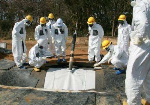 TEPCO officials inspect radioactive reservoirs at the Fukushima Dai-Ichi facility in Okuma, on April 13, 2013