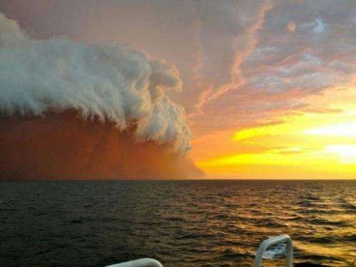 This handout photo taken and posted by Perth Weather Live shows a towering red dust storm over the ocean