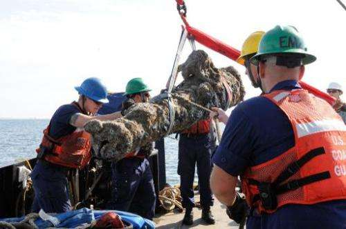 Members of the US Coast Guard and others raise a cannon from a sunken ship on October 28, 2013 off the coast of North Carolina