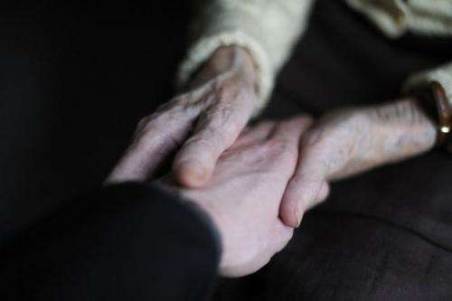 File photo shows a woman suffering from Alzheimer's holding the hand of a relative at a retirement home in France