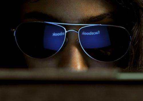 The Facebook logo is seen in a young Indian woman's sunglasses as she browses on a tablet in Bangalore on May 15, 2012