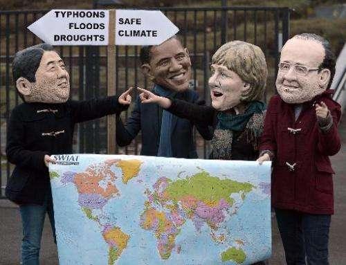 Activists wearing masks of French President Francois Hollande, German Chancellor Angela Merkel, US President Barack Obama and Ja