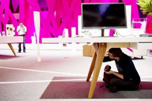 A staff member works on the Deutsche Telekom at the IFA trade fair in Berlin on August 30, 2012