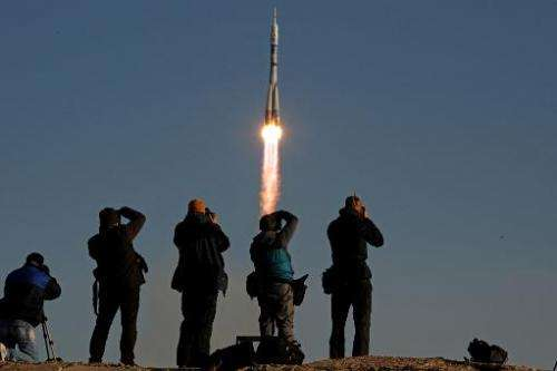People take photographs as Russia's Soyuz TMA-11M spacecraft blasts off from the Russian leased Kazakh Baikonur cosmodrome on No