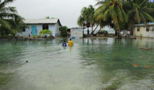 Residents wade through flooding caused by high ocean tides in low-lying parts of Majuro Atoll, Marshall Islandsin 2011