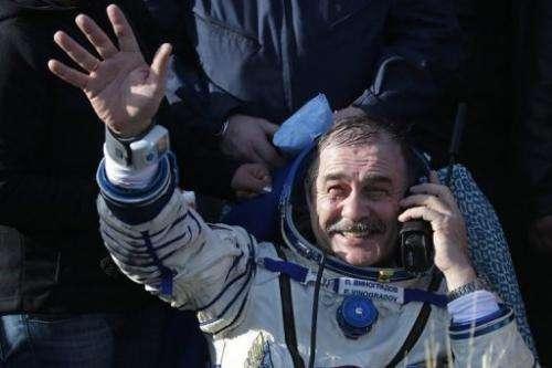 Russian cosmonaut Pavel Vinogradov waves shortly after landing in Kazakhstan on September 11, 2013