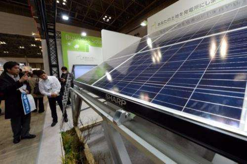 Visitors look at a Sharp solar panel module at the company's booth during the PV Expo in Tokyo, on February 27, 2013