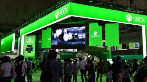 Visitors walk past Microsoft's Xbox One stall at the Tokyo Game Show in Chiba, suburban Tokyo on September 19, 2013