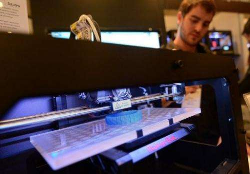 Visitors look at a 3D printer printing an object during an exhibition in New York on April 22, 2013