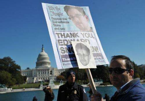Demonstrators hold placards supporting former US intelligence analyst Edward Snowden during a protest against government surveil