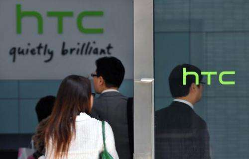 People walk past High Tech Computer Corp. (HTC) logos in Hsintien, Taipei on March 3, 2010