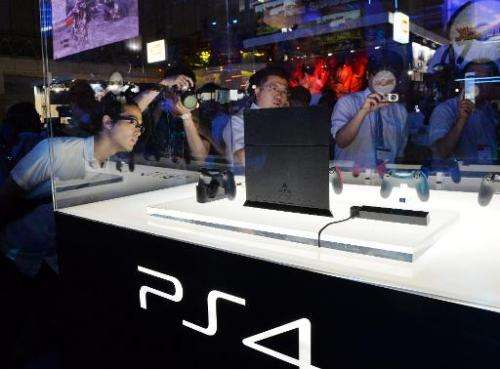 Visitors look at a display case containing Sony Computer Entertainment's PlayStation 4 at the Tokyo Game Show in Chiba, suburban
