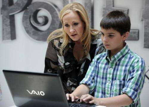 A boy looks at a computer with Harry Potter author J.K. Rowling in London on June 23, 2011