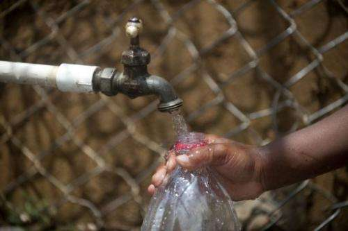 A child fills a bottle with water from a public tap in Colombia on March 22, 2013