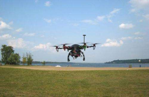 A drone hovers over Petrie Island park in Ottawa, Canada during a demonstration flight on August 21, 2013