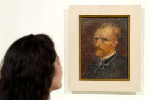 A gallery assistant poses with Vincent van Gogh, Self-portrait (December 1886-January 1887), during an exhibition preview in Lon