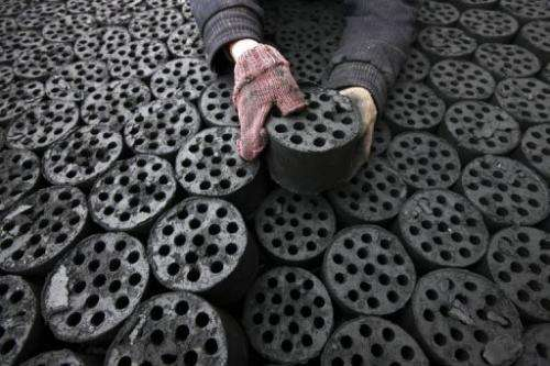 A labourer is seen handling coal briquettes in Huaibei, central China's Anhui province, on January 30, 2013